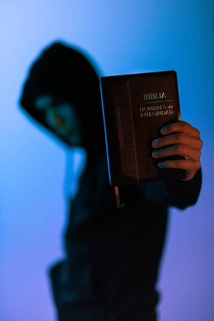 selective focus photography of man holding bible