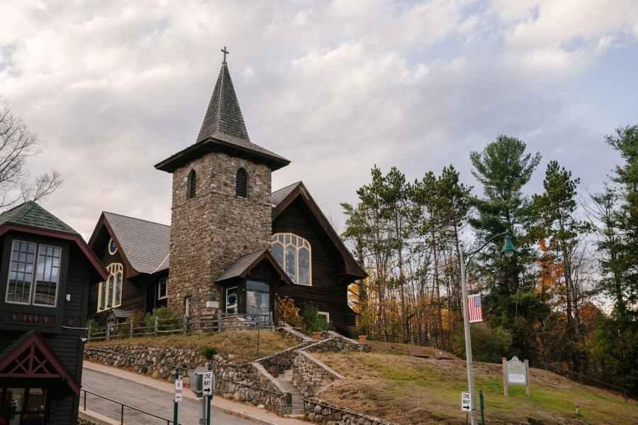 old church facade located on hilly terrain near autumn forest against cloudy sky